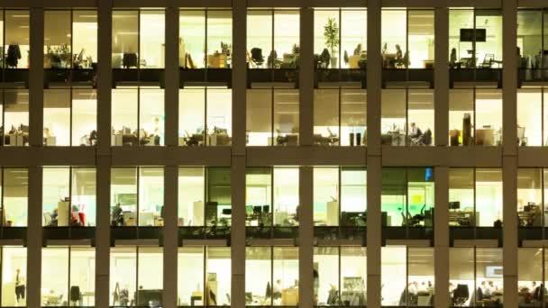 Londýn / Velká Británie - říjen 2016: Včasnost exteriéru kancelářského bloku v noci odhaluje každodenní aktivitu kancelářských pracovníků noční témata rutin pracujících pozdě