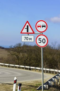 Road signs, speed limits and ban on overtaking at a sharp turn of the highway