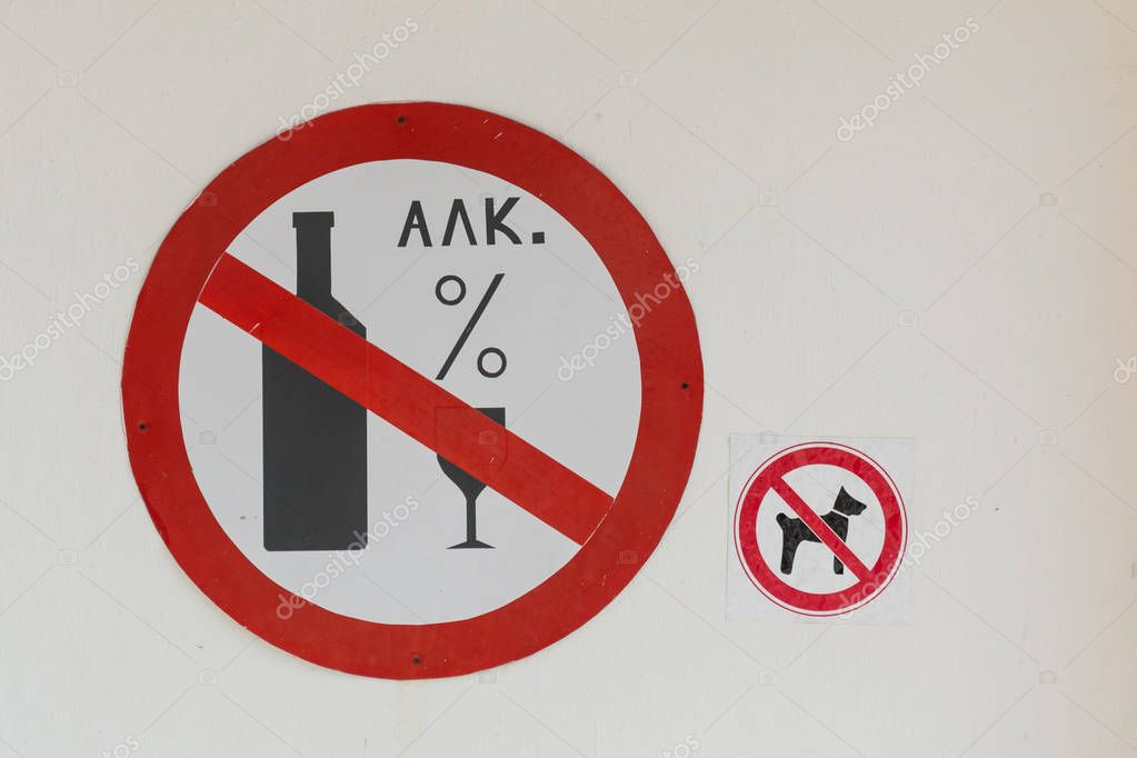 Two signs on the wall banning alcohol and animals on site caf