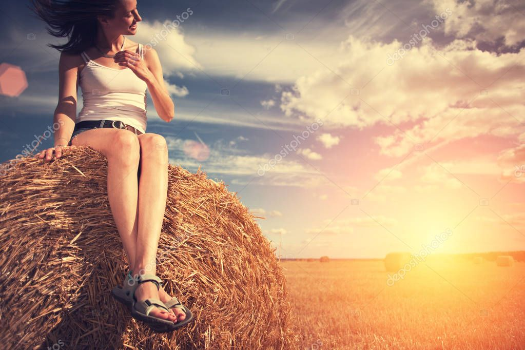 Young girl sitting on a haystack in the field