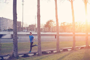 Athlete running in the park at sunset (little motion blur, inten