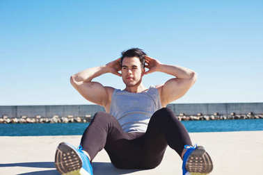Handsome athlete doing abdominal sport exercises outdoors