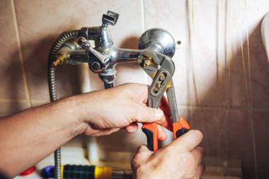 Man repair and fixing leaky old faucet in bathroom
