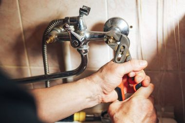 Man repair and fixing leaky old faucet in bathroom