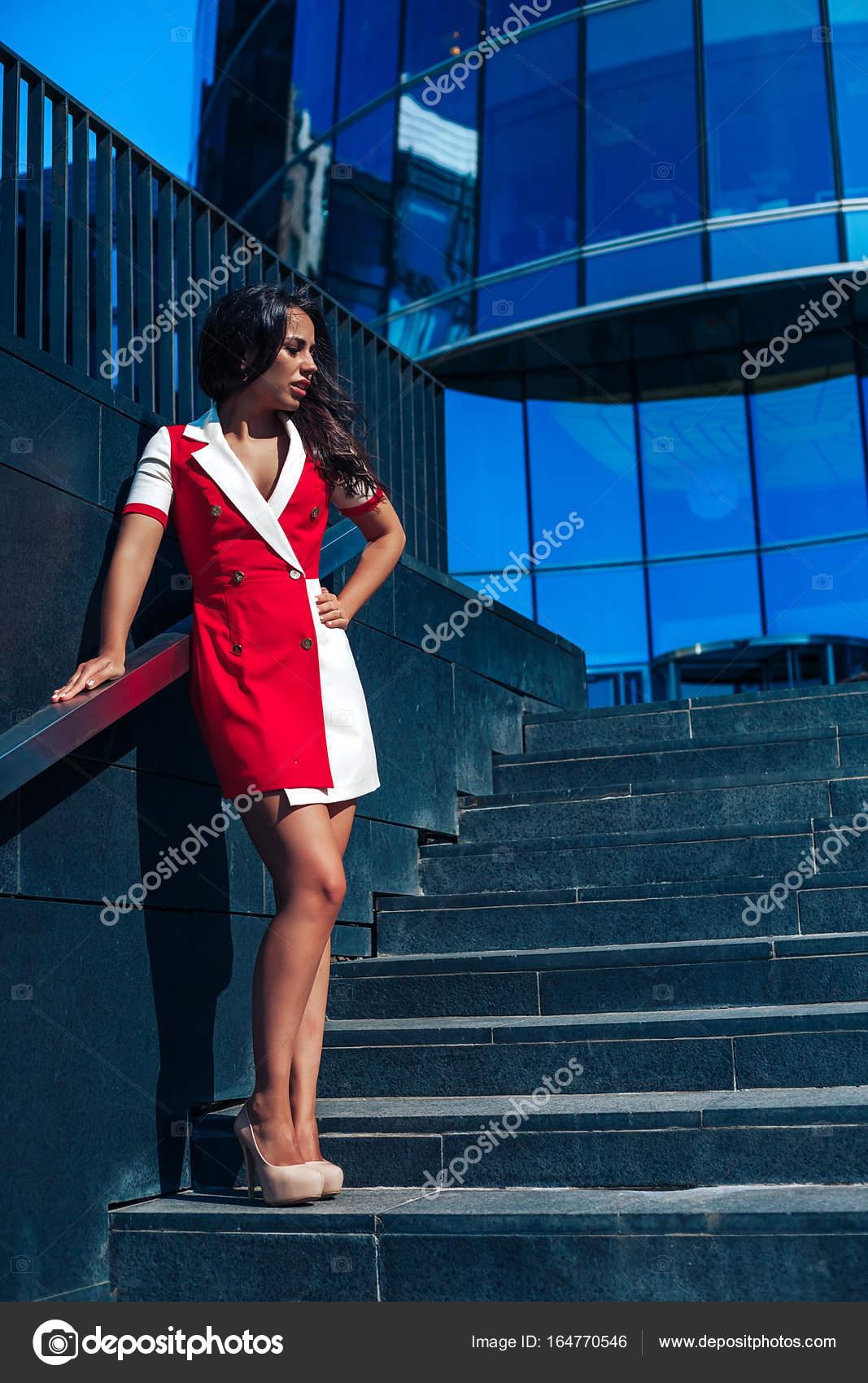 aa94f6211e0885 Mooie glamoureuze brunete meisje in een rode jurk poseren in de buurt van  de showcase van het glas in het Bedrijfscentrum. Zonnevlam in het frame —  Foto van ...