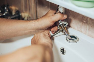 Man services and repairs leaky old faucet on the tap in the bathroom