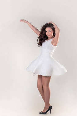 A nice brunette happy girl in a light dress full length in motion on white background
