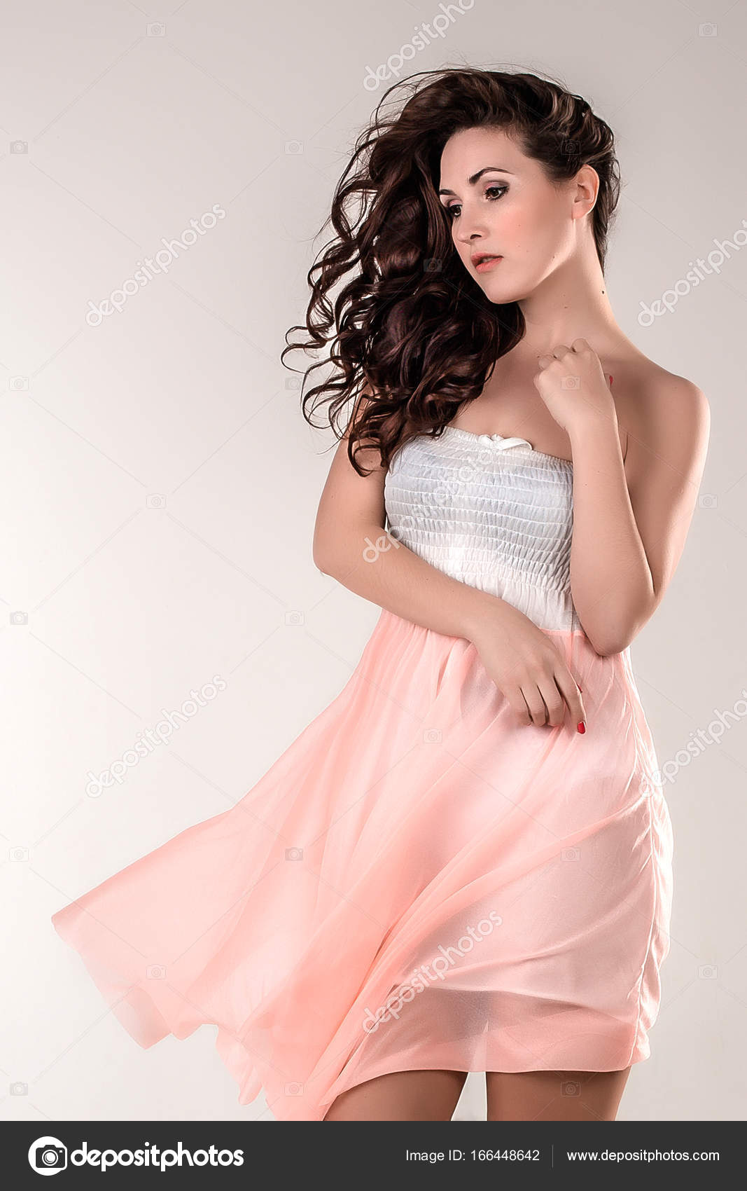 Una chica morena feliz en una Vestido de luz de longitud completa en ...