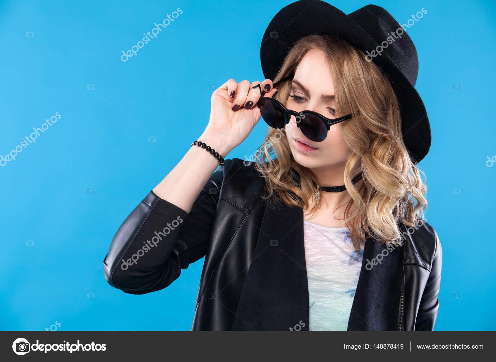 Mujer de moda hipster posando al aire libre en backgrund azul. Negro  sombrero 36c85a14206a
