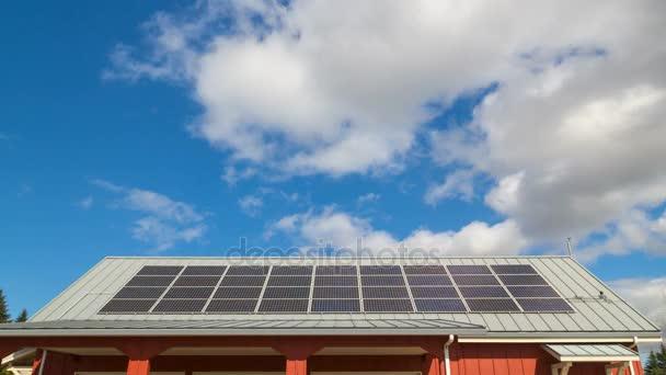 Ultra High Definition 4k Zeitraffer-Film von bewegten weißen Wolken und blauem Himmel über dem Dach mit installierten Sonnenkollektoren 4096x2304 uhd