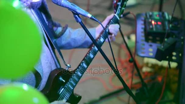 Detail kytarista na rockový koncert