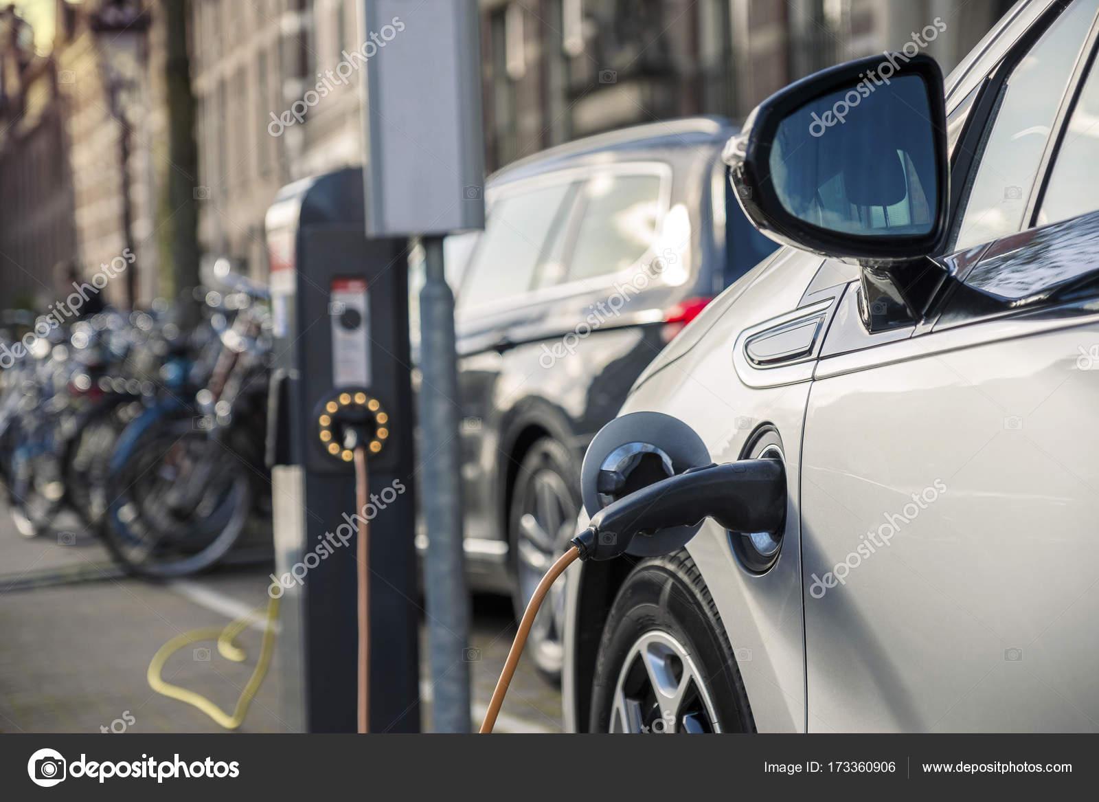 Opladen Van Een Elektrische Auto In Publieke Zender Stockfoto