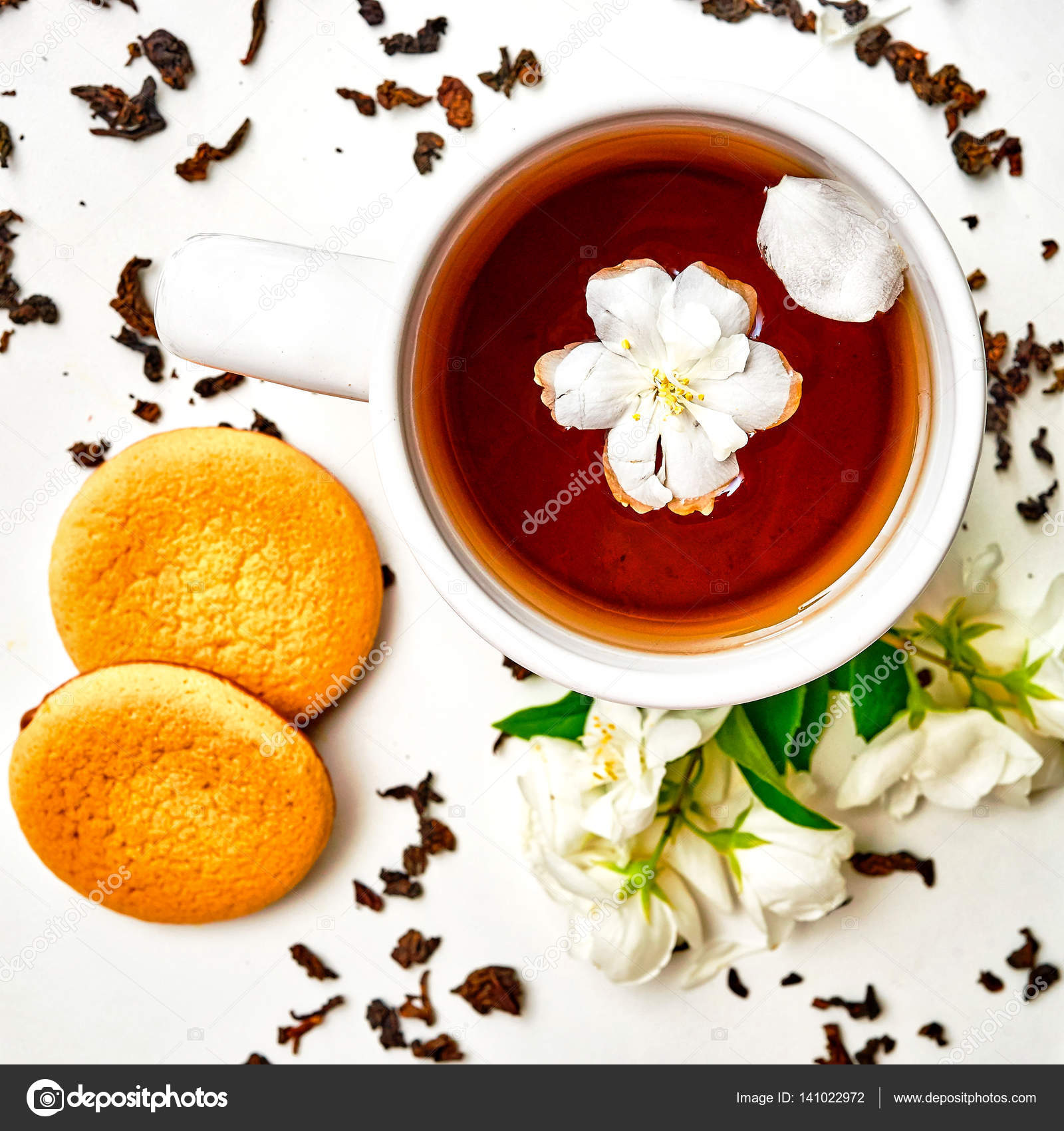 Teacup With Dried And Fresh Jasmine Flowers And Cookie Stock Photo
