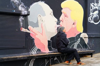 Man at Donald Trump kissing Vladimir Putin mural of Vilnius