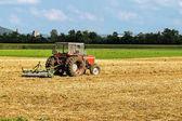 Traktor s pluhem zemědělské sezónní práci v oboru