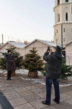 People taking photos at Christmas trees market in Vilnius Lithuania
