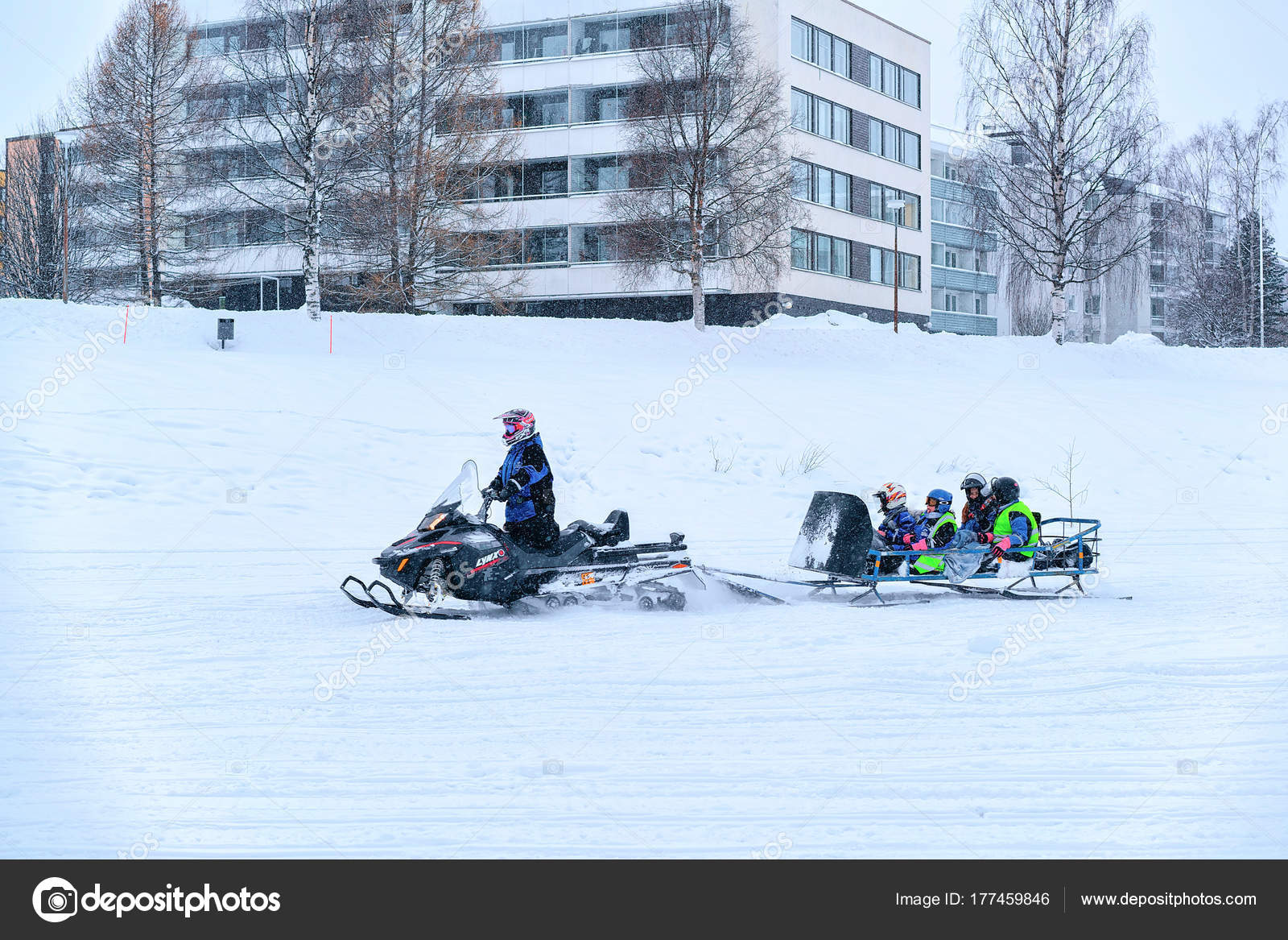 Man riding snowmobile with kids on frozen lake winter Rovaniemi
