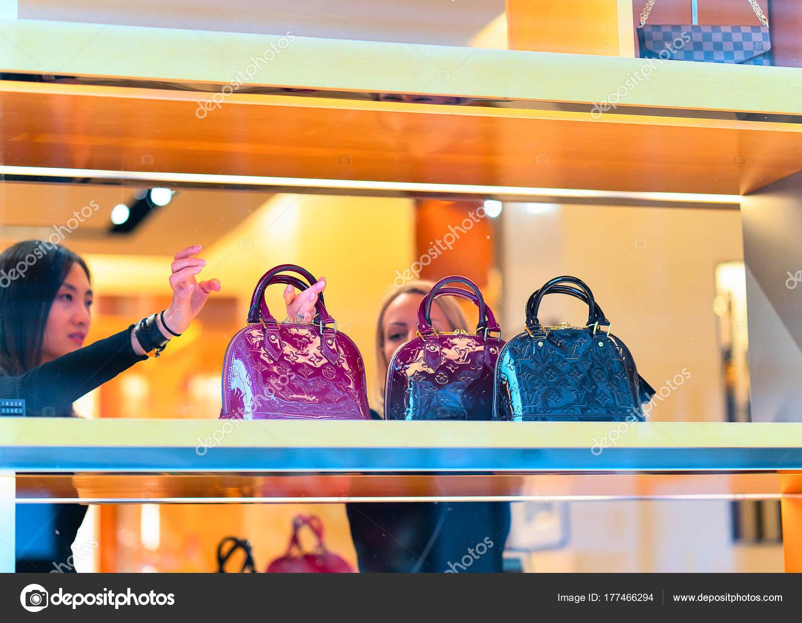 Donne che scelgono borse a mano nel negozio di louis vuitton a