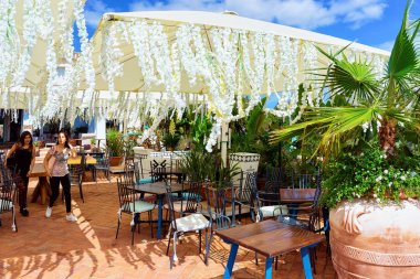 Street cafe with tables and chairs in Porto Cervo