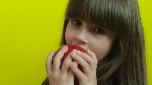 Handsome little girl trying to eat big delicious red apple. Kid eating apple. Yellow background. Close up. Slow motion