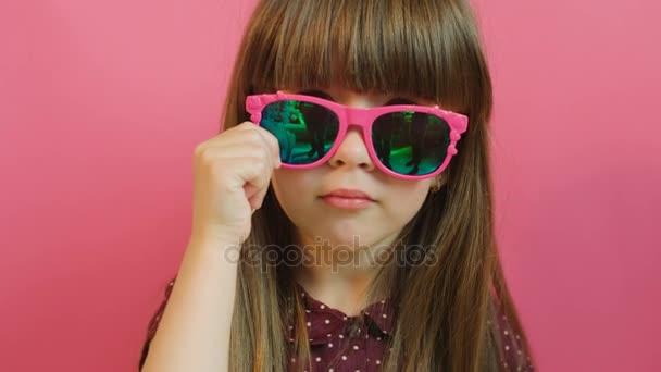 Tvář portrét roztomilá holčička v růžové brýle při pohledu na fotoaparát. Růžový pozadí. Detailní záběr