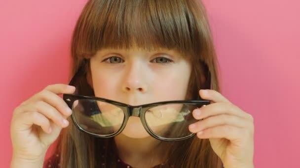 Malá holčička na dospělých brýle. Roztomilá holčička velké brýle a při pohledu na fotoaparát. Portrét shot na růžovém pozadí. Detailní záběr