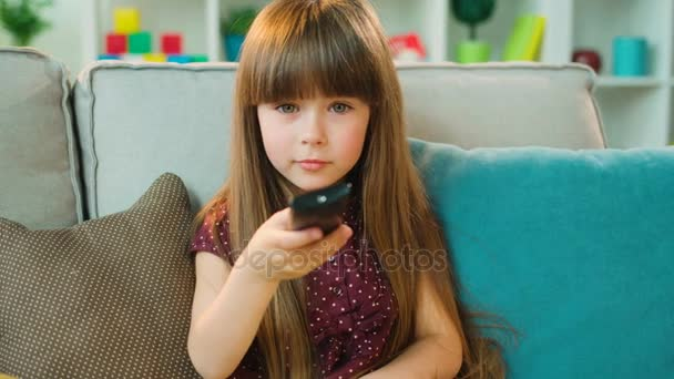 Cute little girl sitting on the couch with remote control and switching  channels  Close up