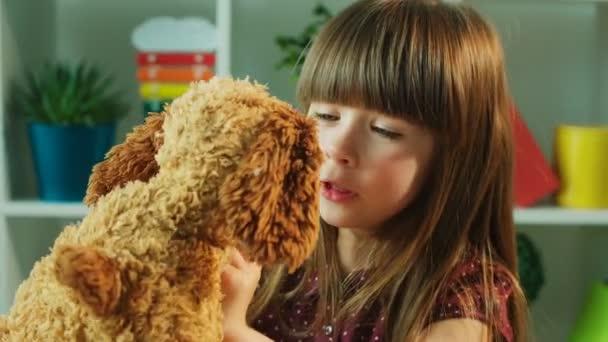 Szép kislány, szerető lány játék mackó. Kis lány átölelte, megcsókolta a mackó. Közelről. Gyerekek szoba