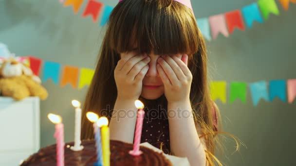 Hezká holčička, takže přání a foukání svíčky na narozeninový dort. Oslava narozenin. Zblízka. Vnitřní, šedé pozadí
