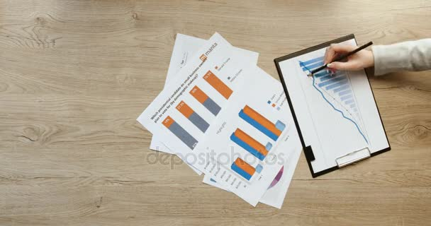 Top view of hands. Business team working with financial charts and graphs, pointing and working with tablet, writing in notebook on office wooden desk. Quick motion. Time lapse