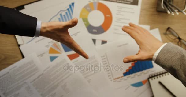Top view of two business men shaking hands at office desk with financial graphs background. Hands top view. Slow motion. Handshake