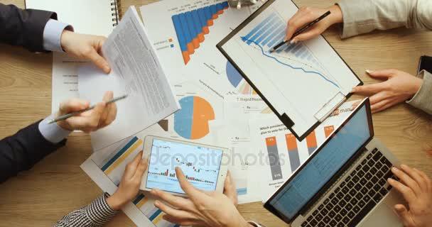 Geschäftsleute prüfen Finanzkarten und Grafiken, zeigen und arbeiten mit Tablet und Laptop, schreiben Notizen am Schreibtisch im Büro. Hände von oben betrachtet. Zeitlupe.