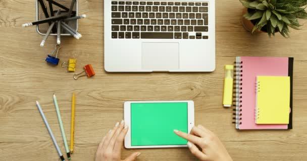 Pohled shora na ruce. Žena, její tabletu pomocí zeleným plátnem, posouvání zprávy, klepnutím na fotografie. Office desk pozadí. Zpomalený pohyb. Red epic