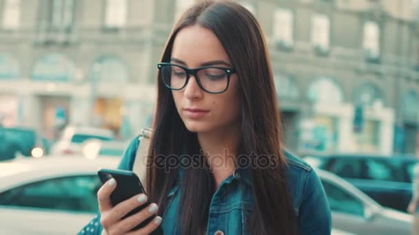 Beautiful woman using app on the smart phone and looking around while walking on the city street. Close up