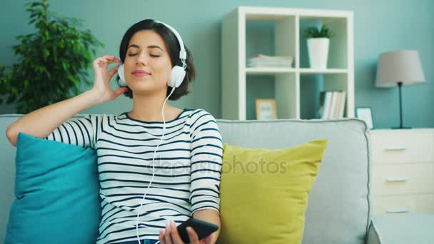 Close up beautiful young woman listening to music in big white headphones from her smart phone. happy woman listening songs