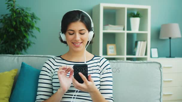 Young woman sitting on the couch in the living room, holding smartphone and listening to music from white headphones. Close up