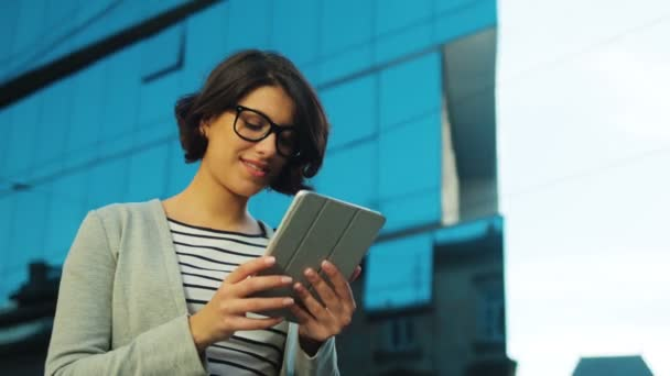 Attractive young business woman using tablet device on the urban city street. Close up.