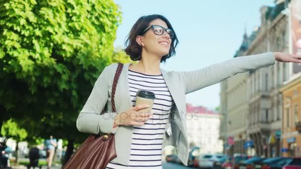 Šťastná mladá žena se snaží zastavit taxi, taxi na ulici města. Žena mává rukou chytit auto
