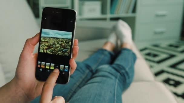 New York - 2017. március 10.: Nő kezében használ photoshop Vsco szerkesztés fénykép otthon a nappaliban.