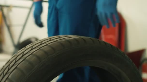 Portrait of automobile tire, when auto mechanic rilling of car tire on autoservice background. Indoor.