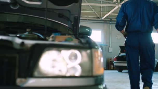 Auto mechanik v modré uniformě držení nástroje a tam u autoservice. Pohled zezadu.