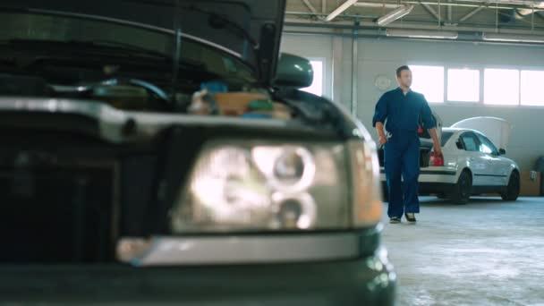 Hezký auto mechanik v modrých uniformách, děje autoservice a v ruce drží klíč. Vnitřní.