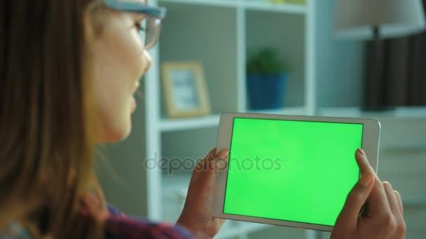 Mladá žena bílé tabletový počítač pomocí zeleným plátnem zatímco sedí na gauči v obývacím pokoji. Žena ruce rolování, posouvání stránky. Chromatický klíč. Zadní boční pohled. Detailní záběr