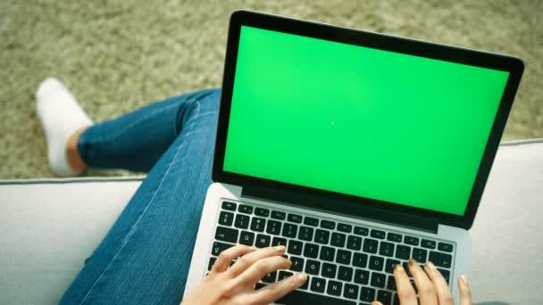 Mladá žena, psaní na klávesnici počítače laptop s zelenou obrazovkou zatímco sedí na gauči v obývacím pokoji. Střílel přes rameno. Pohled shora. Chromatický klíč. Detailní záběr