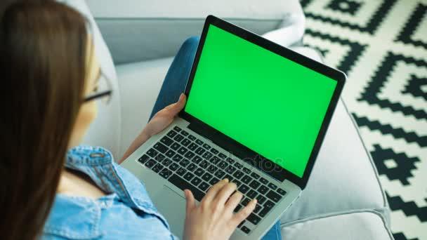 Mladá žena, psaní na klávesnici počítače laptop s zelenou obrazovkou zatímco sedí na pohovce v obývacím pokoji doma. Střílel přes rameno. Chroma klíč