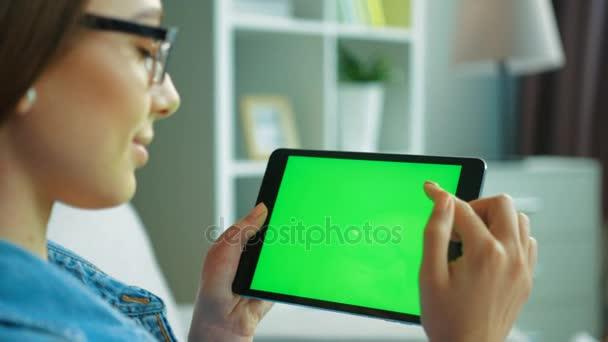 Atraktivní mladá žena černé tabletový počítač pomocí zeleným plátnem zatímco sedí na gauči v obývacím pokoji. Žena ruce posouvání, zvětšování stránky. Chromatický klíč. pohled přes rameno. Detailní záběr