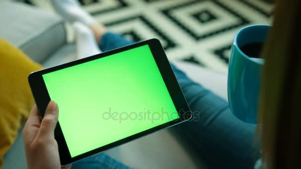 Žena používající zařízení tablet s zeleným plátnem. Žena držící tabletu a pití kávy, zatímco sedí na gauči v obývacím pokoji. Chromatický klíč. Pohled přes rameno. Detailní záběr
