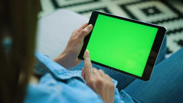 Mladá žena černý tablet zařízení pomocí zeleným plátnem. Žena držící tabletu, posouvání stránky zatímco sedí na gauči v obývacím pokoji. Chromatický klíč. Pohled přes rameno. Detailní záběr