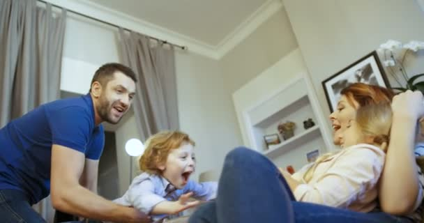 Happy family spending time together at home. Father playing with his daughter, mother holding son on her knees. Mother, father, son, daughter. Family laughing