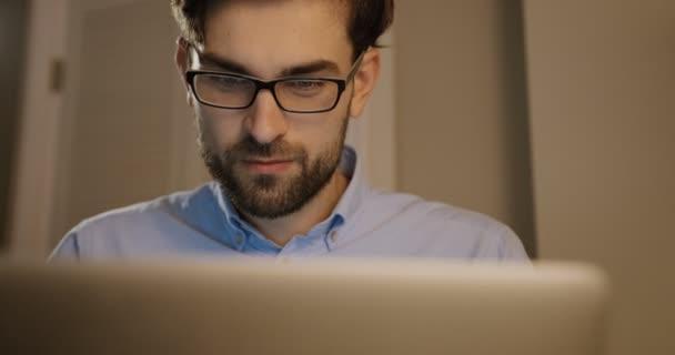 Krásný muž v brýlích, psaní na jeho notebooku. Obchodní muž pracuje na úřadu pozadí. Detailní záběr.